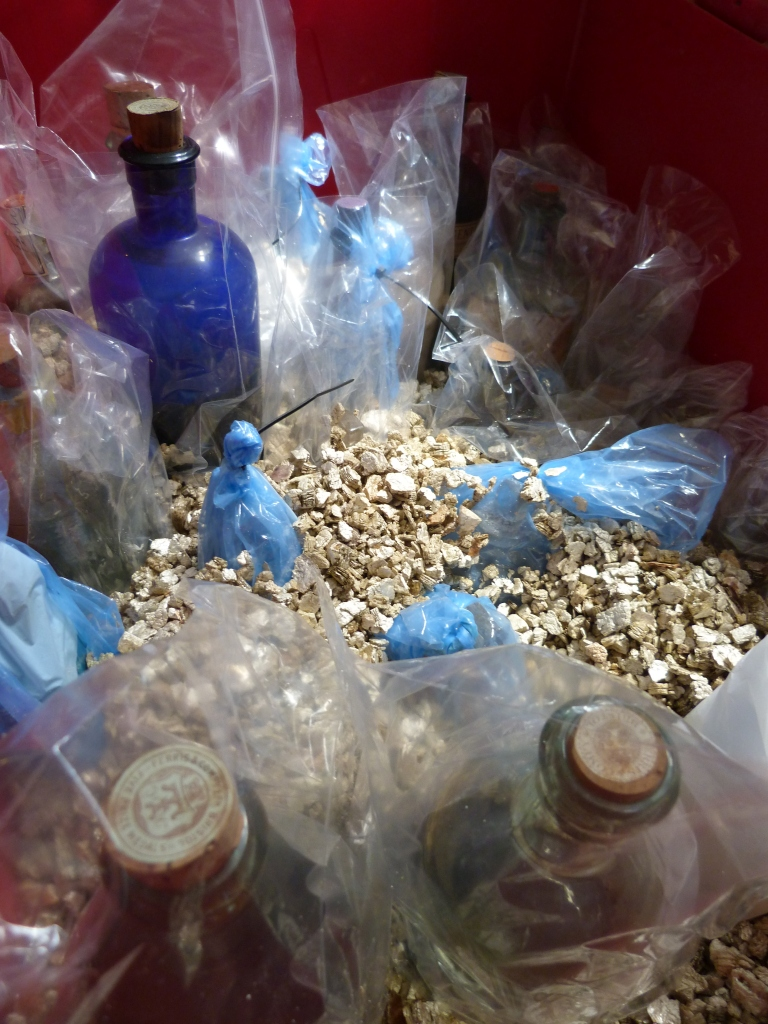 The bottles are wrapped and sealed and placed in a bed of vermiculite; the vermiculite holds the bottles in place and also acts as an absorbent to mop up spillages.