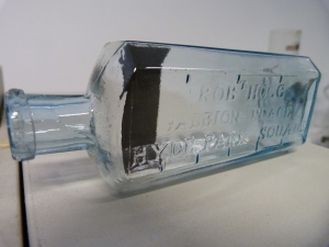 A light blue bottle, embossed with the name of the contents as well as markers for measures.