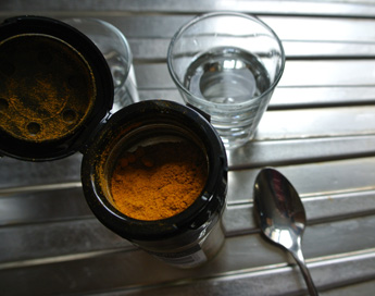 Water, turmeric and spoon.